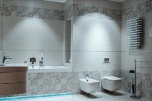 Wnętrze jasnej, białej łazienki z moizaiką w salonie w Piekarach Śląskich